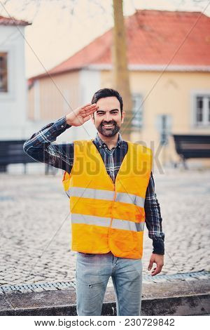Portrait Of A Smiling Man In An Orange Life Jacket On The Street Salutes With A Hand To His Head. A