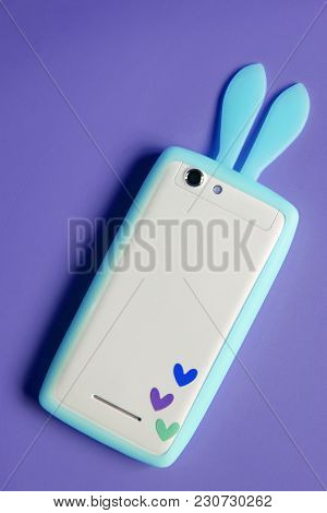 White Phone With Blue Bunny Ears And Three Little Colorful Hearts On Violet Purple Background With C