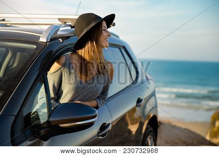 Beautiful woman looking out the car window, near the beach