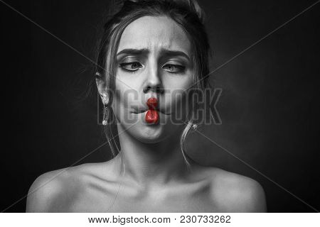 Fun Girl On Black Background Looking At Nose Making Grimace With Her Lips