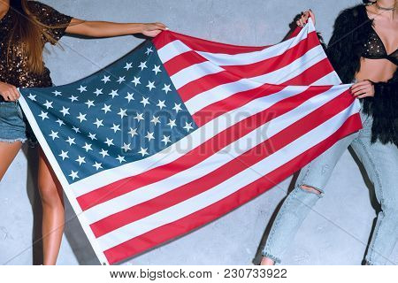 Partial View Of Women Holding American Flag In Hands Against Concrete Wall