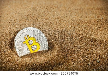Bitcoin Coin Buried In The Sand. Bitcoin Is The Most Popular Cryptocurrency In The World. Bitcoin Is