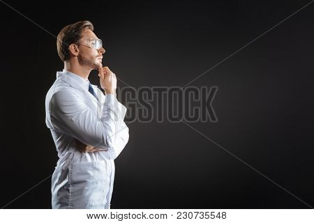Strange Accident. Thoughtful Occupied Bespectacled Scientist Standing In The Dark Room Touching To H