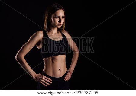 Sporty Muscular Female Doing Workout With Dumbbells Isolated On Black Background. Athletic Young Wom
