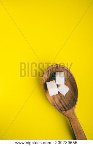 Closeup Top View Of White Cubes And Sugar In Spoon On Bright Yellow Background