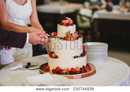 The Bride And Groom Cut A Beautiful Wedding White Cake Decorated With Berries, Fizalis And Pumpkins.