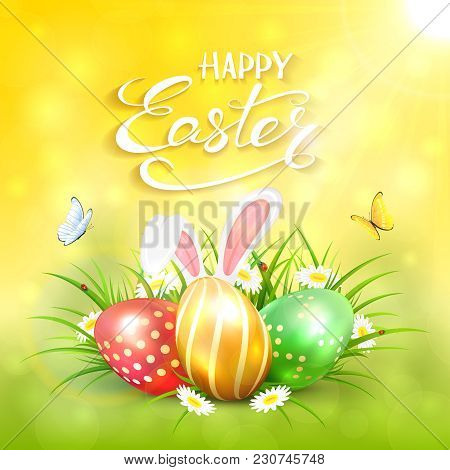 Three Colorful Easter Eggs With Rabbit Ears On Grass And White Flowers. Yellow Nature Background Wit