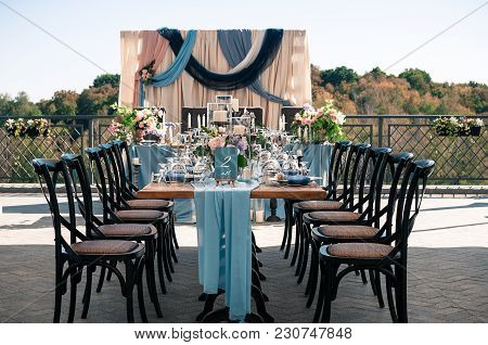 Wedding Catered Event Setting, Flowers, Candles, White Plates, Blue Napkins, Wooden Tables, Event De