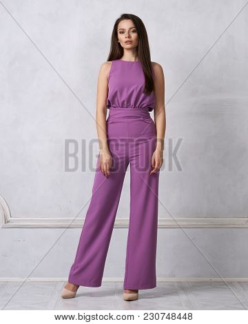Charming Female Model With Long Brunette Hair Wearing Fashionable Sleeveless Purple Jumpsuit And Hee