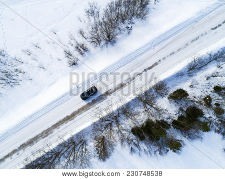 Aerial View Of A Car On Winter Road. Winter Landscape Countryside. Aerial Photography Of Snowy Fores