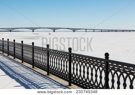 The Metal Fence On The Waterfront. Winter Day. Road Bridge Between The Cities Of Saratov And Engels.