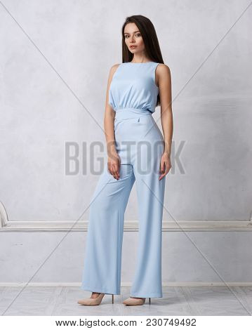 Charming Female Model With Long Brunette Hair Wearing Fashionable Sleeveless Blue Jumpsuit And Heele