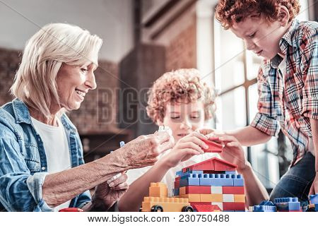 Having Fun. Joyful Nice Aged Woman Sitting At The Table And Playing With Her Grandchildren While Enj