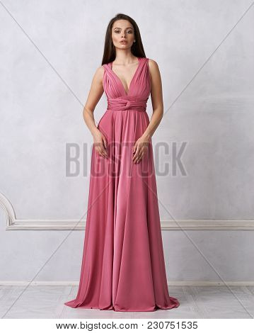 Beautiful Long Haired Young Woman Dressed In Stylish Red Bandeau Maxi Dress Posing Against White Wal
