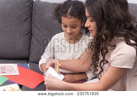 African American Mother And Daughter Cutting Paper For Greeting Card On Mothers Day
