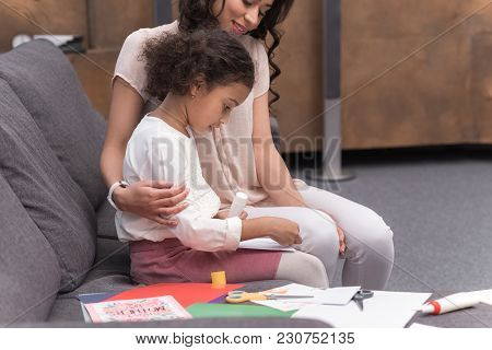 Side View Of African American Daughter Making Greeting Card On Mothers Day