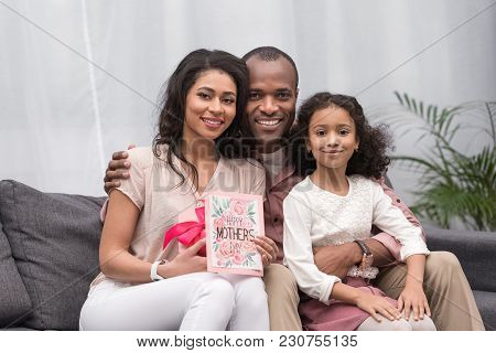 African American Parents And Daughter Looking At Camera On Mothers Day
