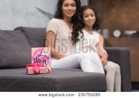 African American Daughter And Mother With Gift And Postcard Of Mothers Day On Foreground
