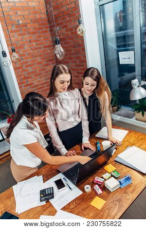 Three Female College Students Working On Assignment Together Using Laptop Standing At Home.