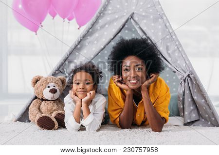 African American Mother And Daughter Resting Chins On Hands And Looking At Camera At Home