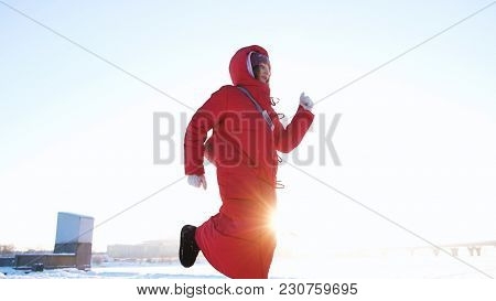 Funny Girl In A Red Down Jacket Dancing In The Winter At Sunset, Slow Motion