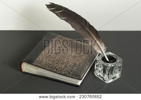Old Book And Quill Pen With Inkwell On The Table. Free Copy Space. Education Concept.