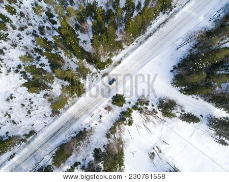 Aerial View Of A Car On Winter Road. Winter Landscape Countryside. Aerial Photography Of Snow Forest