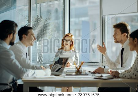 Exchanging Ideas. Upbeat Young Colleagues Sitting At The Table Facing Each Other And Discussing The