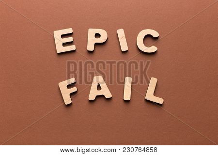 Epic Fail Phrase Spelled With Wooden Letters On Brown Background, Copy Space, Top View. Crisis, Fail