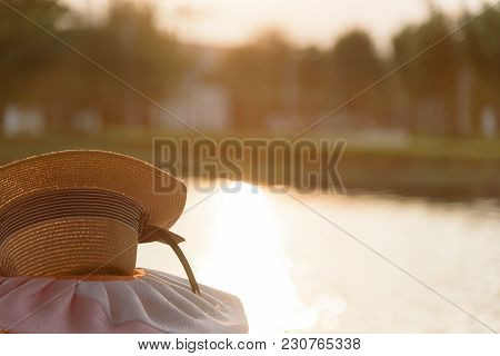 Brown Hat At Garden Park And River In The Evening With Sunset Time.