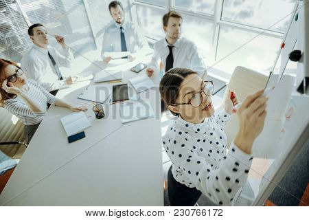 Helpful Visualization. Pleasant Young Woman Writing On A Whiteboard While She Delivering A Presentat