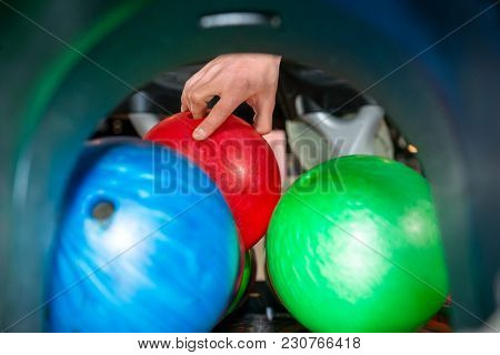 Close-up of man's hand picking up bowling ball from rack in club