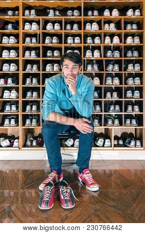 Portrait of serious young man sitting against bowling shoe rack