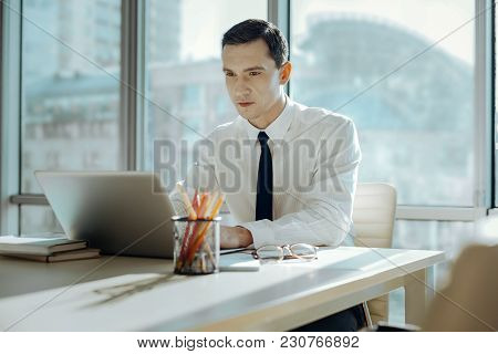 Immersed In Work. Handsome Black-haired Young Man Sitting At The Table In His Office And Working On