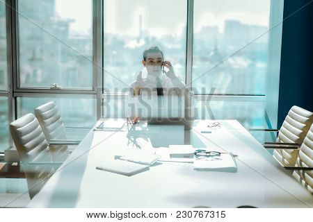 Important Conversation. Pleasant Young Executive Sitting At The Table In The Office And Talking On T