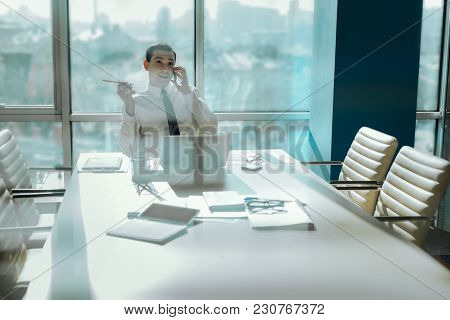 Pleasant Chat. Upbeat Young Worker Sitting At The Empty Table In The Conference Room And Chatting Ha