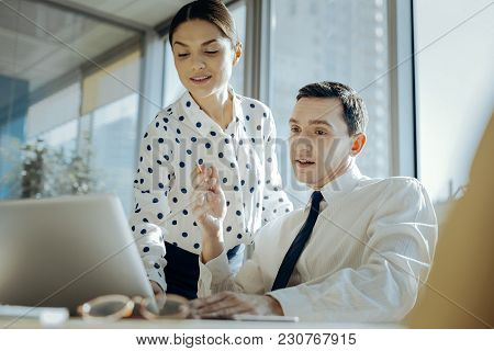 Important Tips. Pleasant Young Woman Checking Her Colleagues Presentation On The Laptop And Giving H