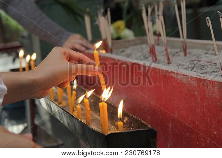 Buddhists Make Merit,placing A Lighted Candle And Lit Incense With Candles Frame On The Altar Of Bud