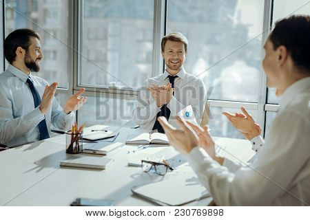 Great Achievement. Cheerful Young Businesspeople Sitting At The Table In The Conference Room And Cla