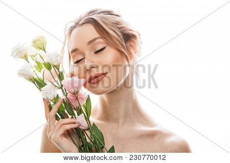 Amazing woman 20s with tied auburn hair posing with bouquet of beautiful flowers isolated over white background