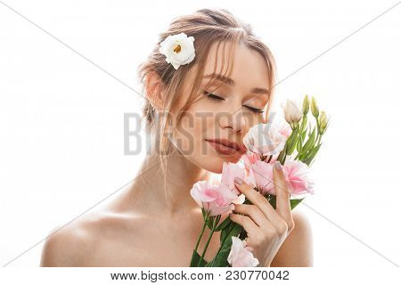 Sensual young woman 20s with tied auburn hair holding and smelling beautiful eustoma flowers isolated over white background