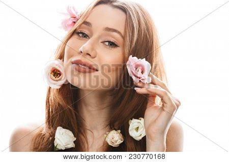 Photo of adorable woman model 20s with makeup looking on camera and touching aroma tulip gentian flowers in her long auburn hair isolated over white background