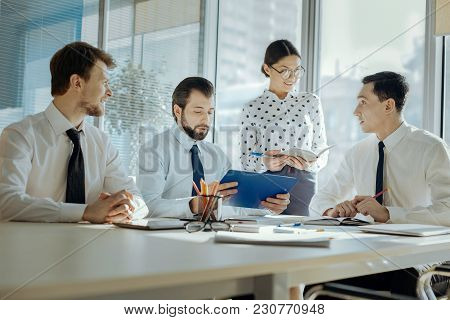 Prospective Project. Pleasant Young Business People Sitting In The Conference Room And Discussing Co