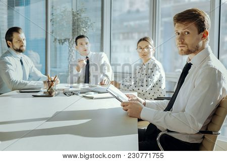 Ready For Scolding. Handsome Young Manager Sitting At The Meeting With The Board Of Directors And Lo
