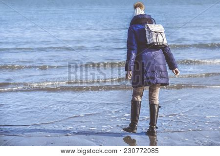 Girl Wearing Winter Clothes Walk In Sea Shore  Back View With Boots And Backpack