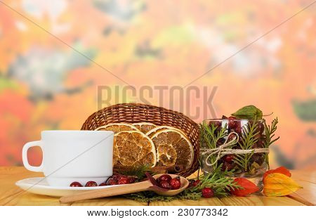 Dry Orange Slices In Basket, Bowl Full Of Rose Hips, Cup, Saucer And Spoon On Beige Wooden Table