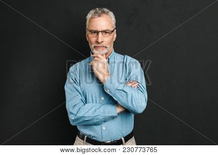 Portrait of a thoughtful mature man dressed in shirt looking at camera over black background