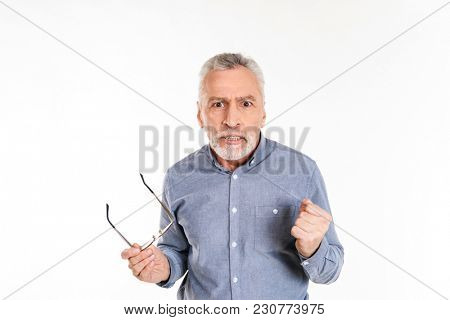 Angry displeased mature man taking off glasses and looking camera seriously isolated over white