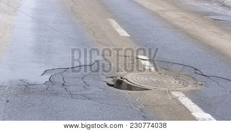 Pothole In Asphalt Near The Sewer Hatch, In The Middle Of The Street.