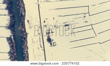 Drop Down View Of River Passing Snow Covered Fields. Aerial Photography.
